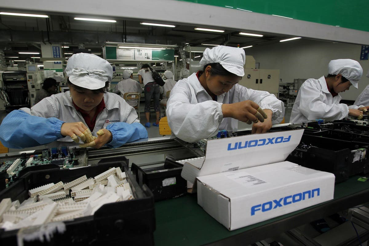 Staff members work on the production line at the Foxconn complex in the southern Chinese city of Shenzhen, southern China.  (AP)
