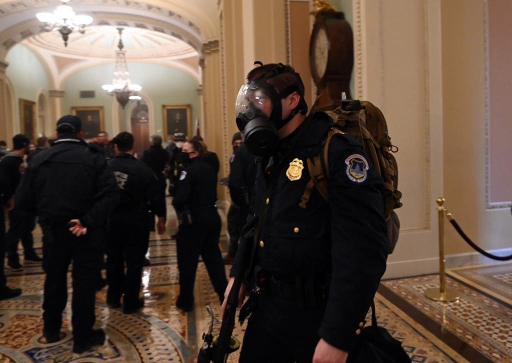 A US Capitol police officer wears a gas mask as supporters of US President Donald Trump enter the Capitol on January 6, 2021, in Washington, DC.