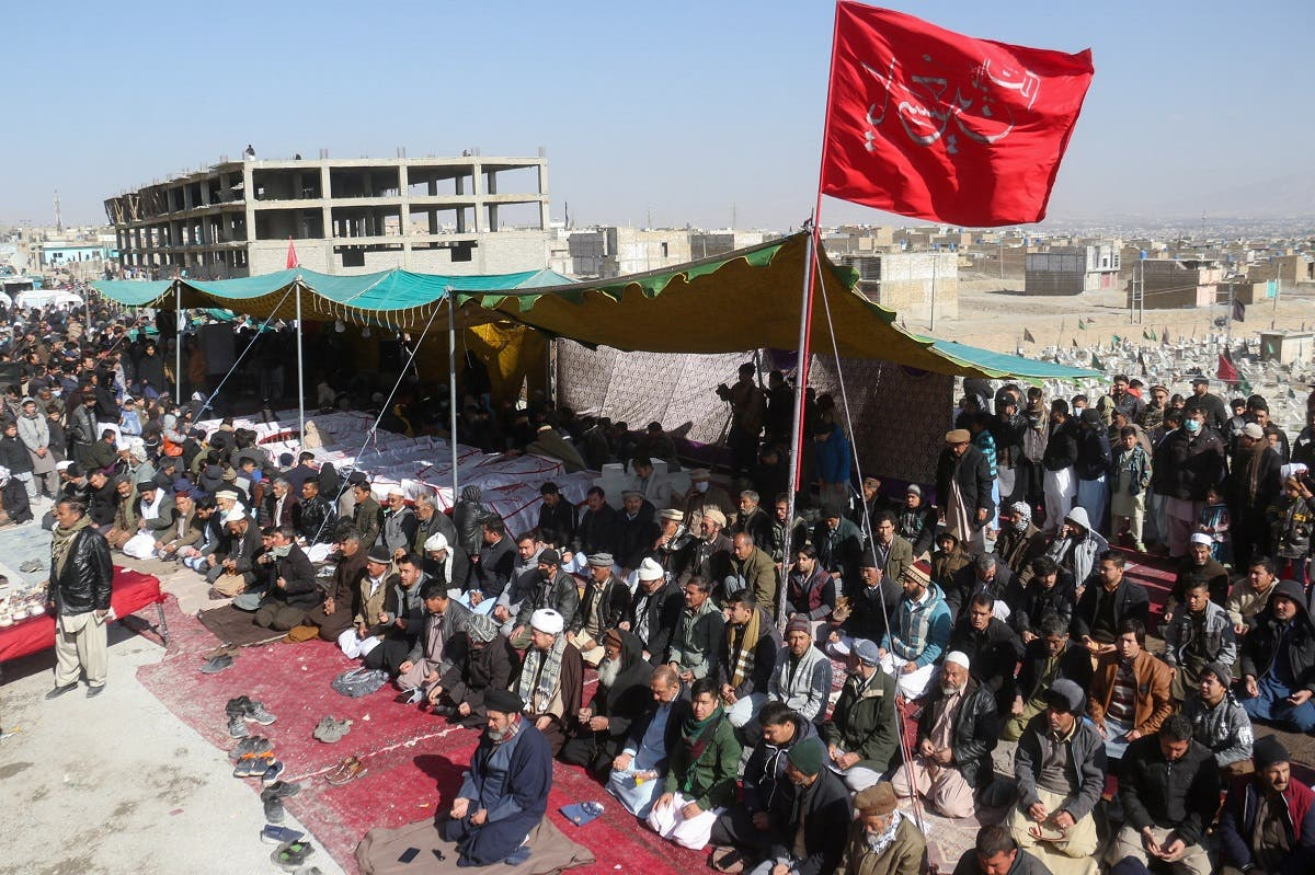 People offer prayers beside a tent with the bodies of coal miners from Pakistan's minority Shi'ite Hazara community, who were killed in Mach area of Bolan district, as they protest demanding justice, in Quetta, Pakistan January 5, 2021. (Reuters)