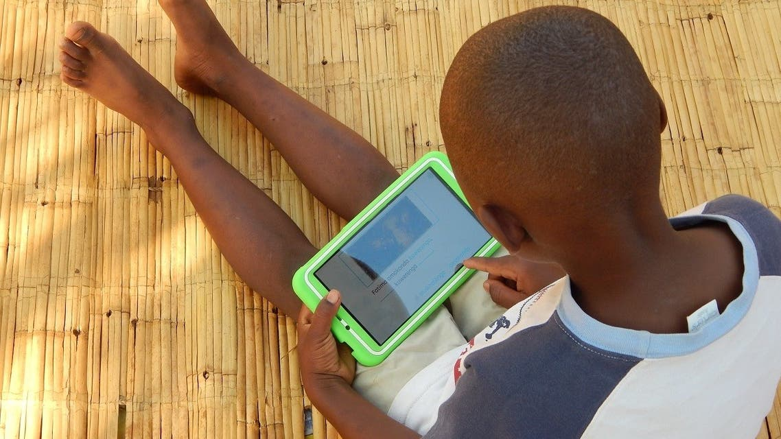 Eight-year-old Elijah Chiseka uses a learning tablet provided by the charity Voluntary Service Overseas in Gumulira village in western Malawi, September 23, 2020. (Credit VSO/Charity Kanyoza via Reuters)