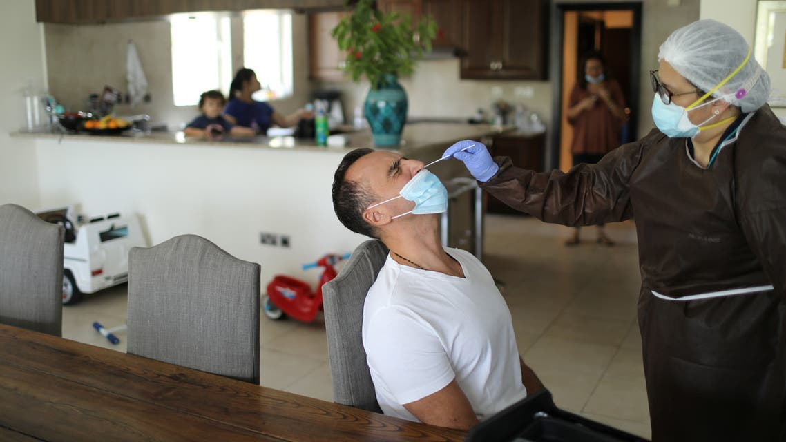 A worker of a company, which is offering testing for the coronavirus disease (COVID-19) and check-in for travellers at their homes, wears a protective mask as she takes a swab sample in Dubai, United Arab Emirates July 13, 2020.