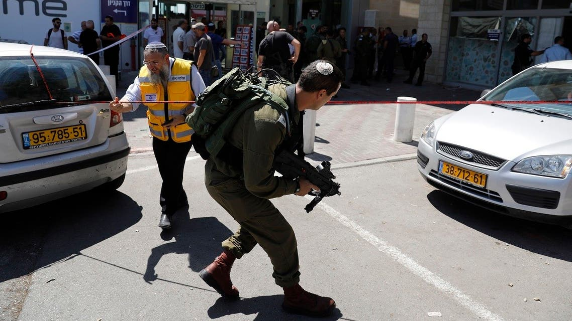 A file photo shows Israeli forensic police and soldiers inspect the place where an Israeli man was stabbed by a Palestinian near the entrance to a mall at the Gush Etzion junction in the occupied West Bank, September 16, 2018. (Ahmad Gharabli/AFP)