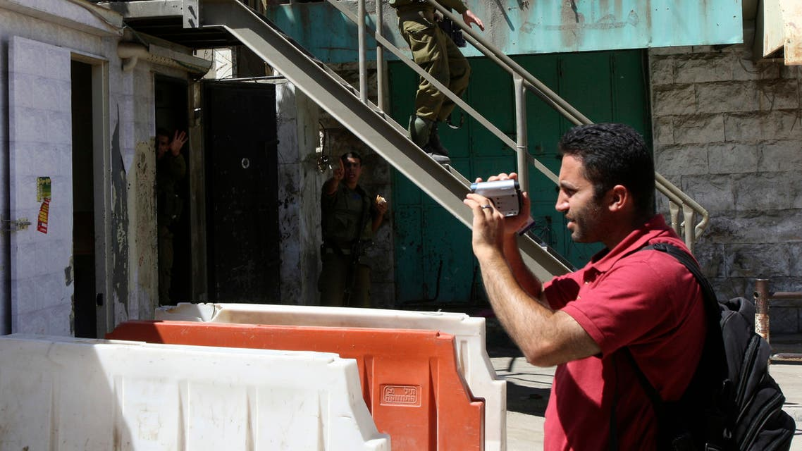 Issa Amro shoots video near Israeli soldiers in the West Bank city of Hebron on August 11, 2008. (Reuters)