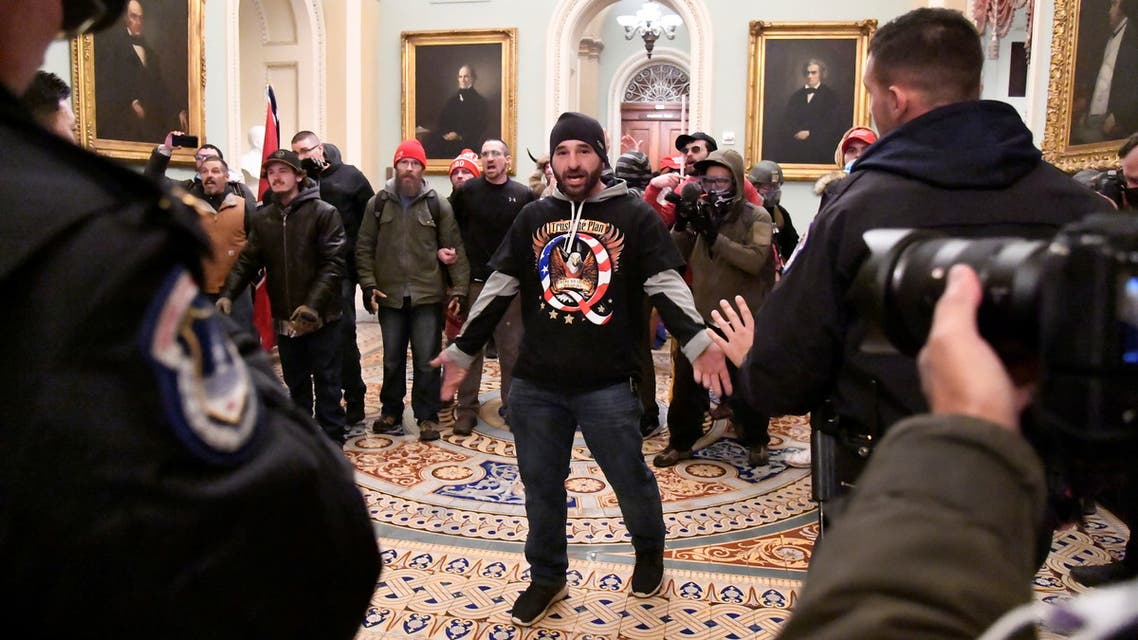 A supporter of President Donald Trump confronts police as Trump supporters demonstrate on the second floor of the U.S. Capitol near the entrance to the Senate after breaching security defenses, in Washington, US, January 6, 2021. (Reuters)