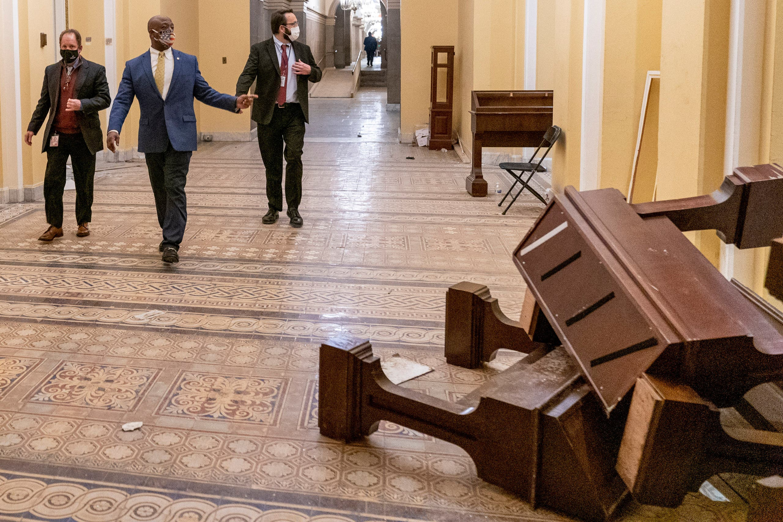 Sen. Tim Scott, R-S.C., second from left, walks past damage in the early morning hours of Thursday, Jan. 7, 2021, after protesters stormed the Capitol in Washington, on Wednesday. (AP Photo/Andrew Harnik)