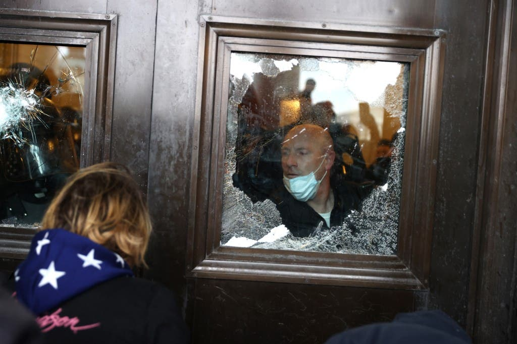 Capitol police officer looks oout of a broken window as protesters gather on the U.S. Capitol Building on January 06, 2021 in Washington, DC. (AFP)