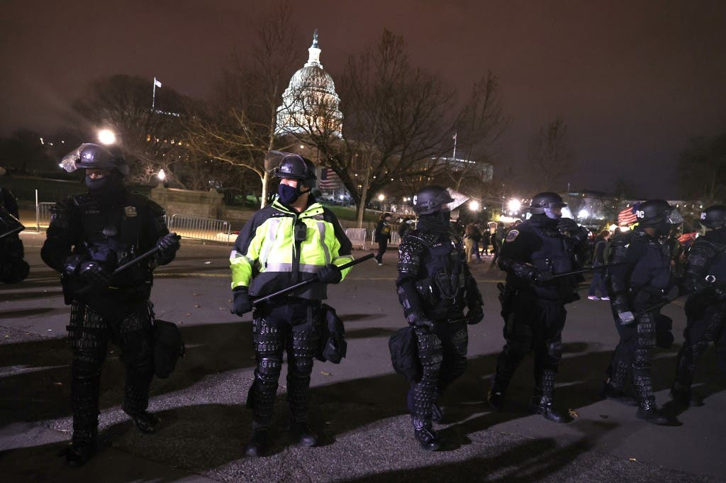 Police officers in riot gear monitor protesters who are gathering at the U.S. Capitol Building on January 06, 2021 in Washington, DC. (AFP)