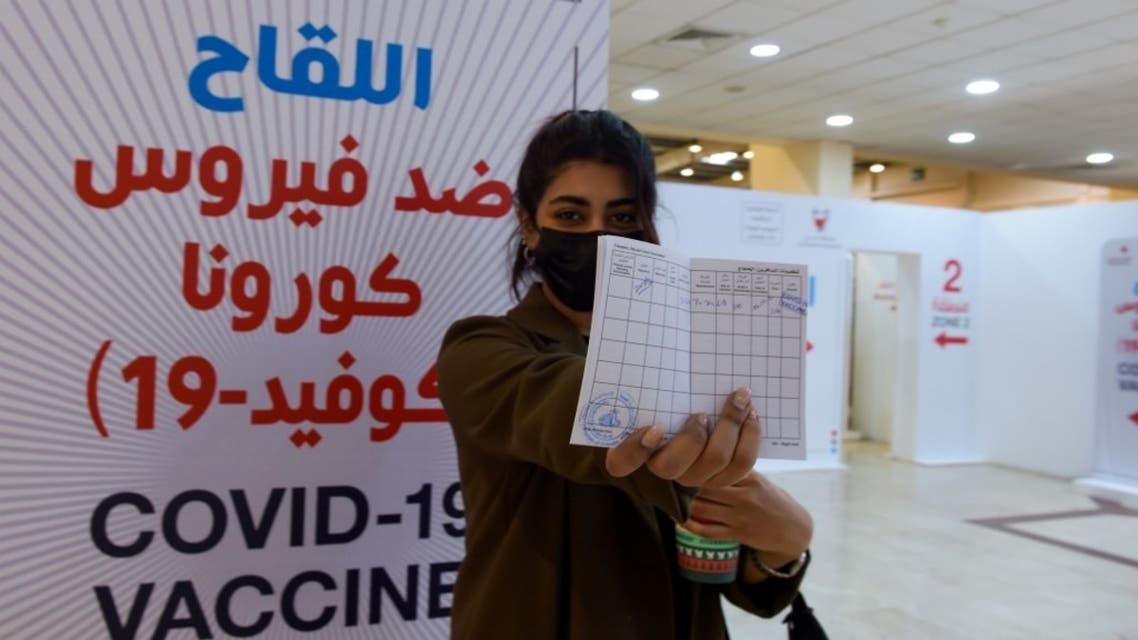 فتاة تحمل شهادة التطعيم ضد فيروس كورونا في البحرين - فرانس برس