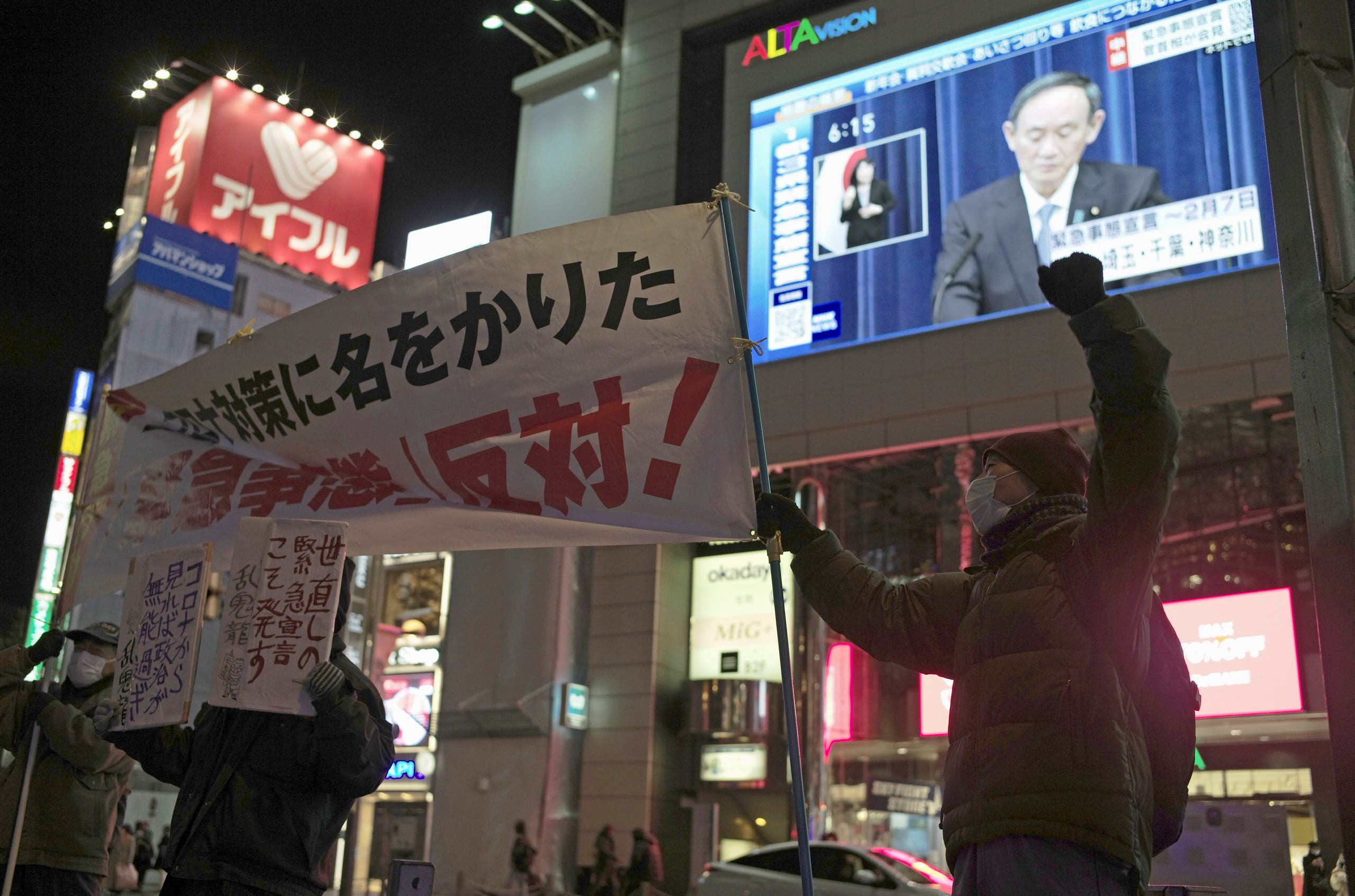 Protesters chant slogans against a state of emergency as Japanese Prime Minister Yoshihide Suga shown on a billboard screen speaks of a state of emergency in Tokyo on Thursday, Jan. 7, 2021.(AP)