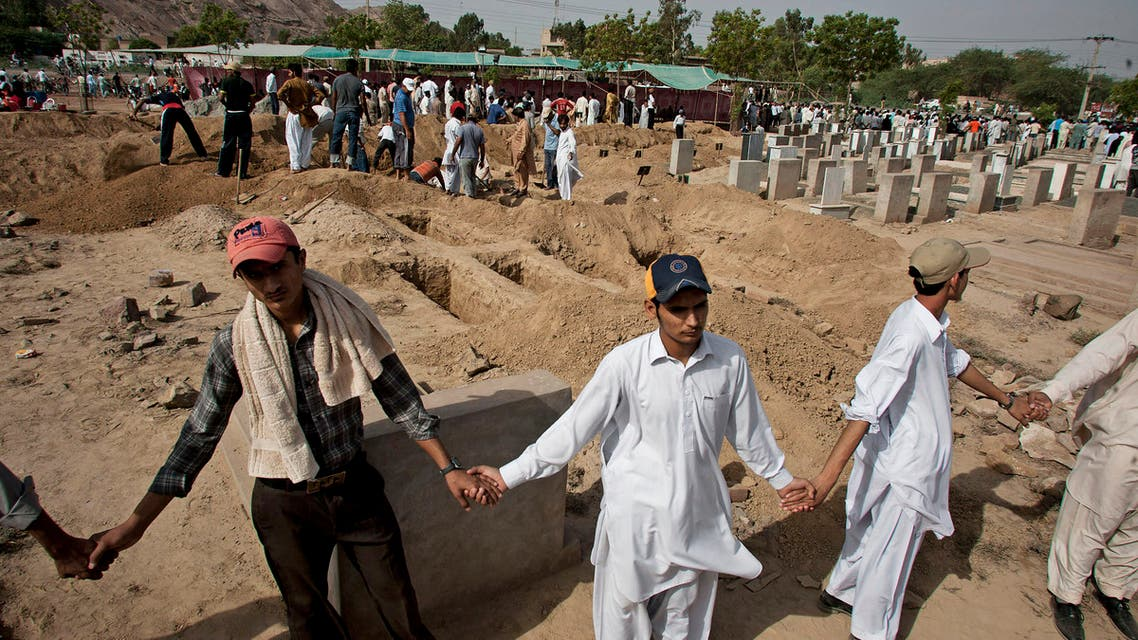 People from a minority Muslim Ahmadi Community stand guard as others preparing to bury the victims of attack by militants, in Rubwah, Pakistan. (AP)