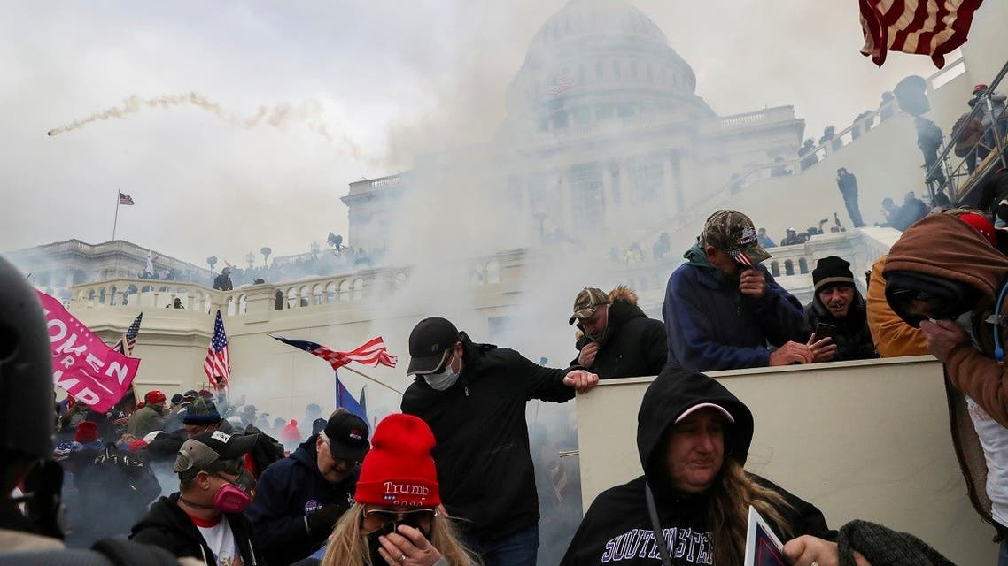Supporters of President Trump cover their faces to protect from tear gas during a clash with police officers in front of the US Capitol Building in Washington, US, January 6, 2021. (Reuters)