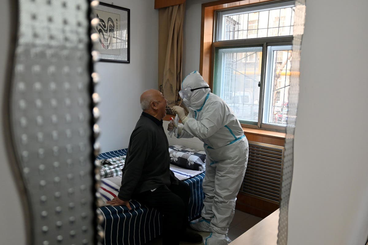 A medical worker in protective suit collects a swab from an elderly man during a door-to-door nucleic acid sampling following a recent coronavirus outbreak in Shijiazhuang, Hebei province, China, on January 7, 2021. (Reuters)