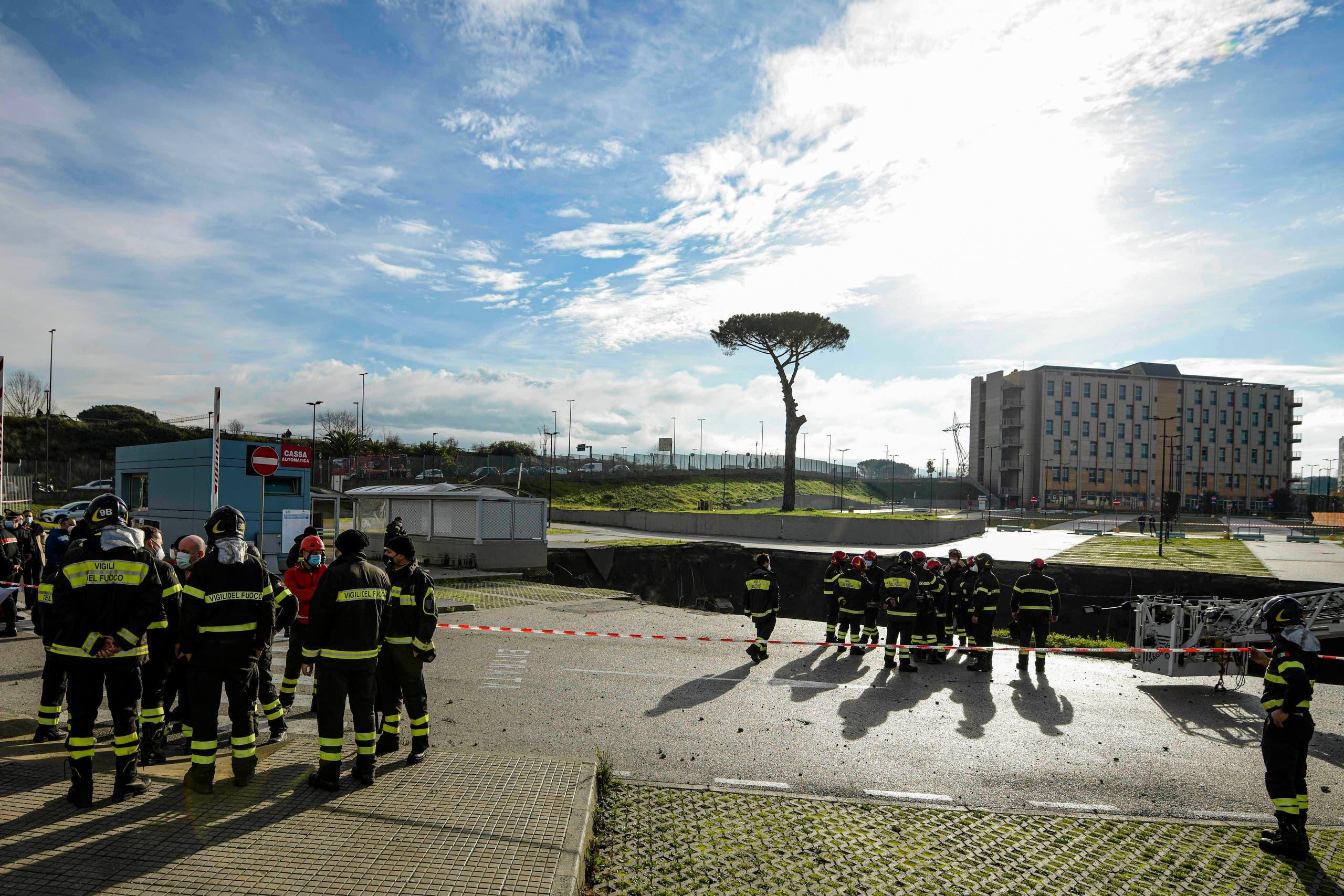 Firefighters stand on the border of the large sinkhole that opened overnight in the parking of Ospedale del Mare hospital in Naples, Italy, Friday, Jan. 8, 2021. A giant sinkhole opened Friday in the parking lot of a Naples hospital, forcing the temporary closure of a nearby residence for recovering coronavirus patients because the electricity was cut. (Alessandro Pone/LaPresse via AP)