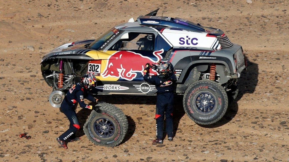 X-Raid Mini JCW Team's Stephane Peterhansel and Co-Driver Edouard Boulanger attend to their car during stage 3. (Reuters)