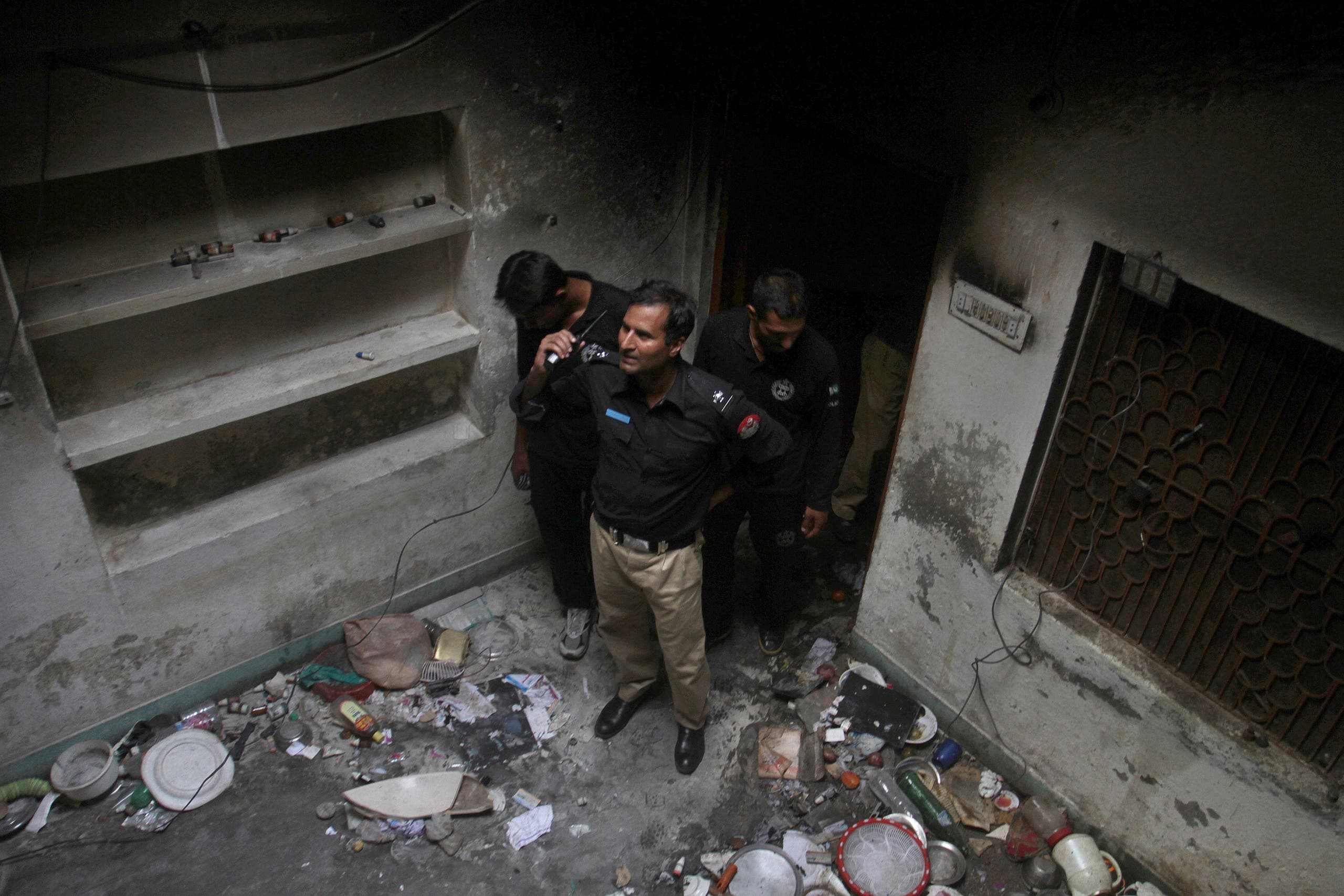 Pakistani police officers examine the house of a family belonging to the Ahmadi sect, which was torched by angry mob following rumors about blasphemous postings on Facebook, in Gujranwala, Pakistan. (AP)