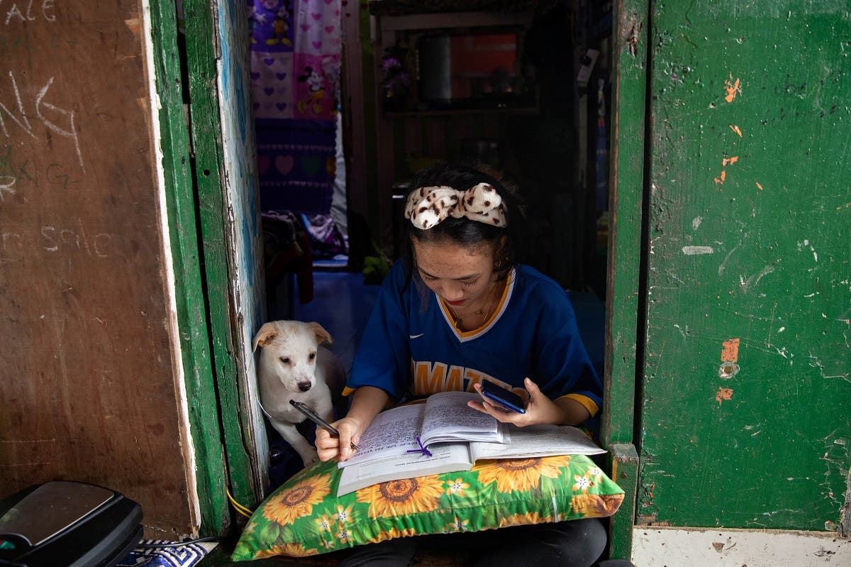 Annie Sabino, 16, a grade 9 student, completes her school work next to her dog, while tending to her family's sidewalk eatery beside their home, as schools remain closed during the coronavirus disease (COVID-19) outbreak, in Manila, Philippines. (Reuters)