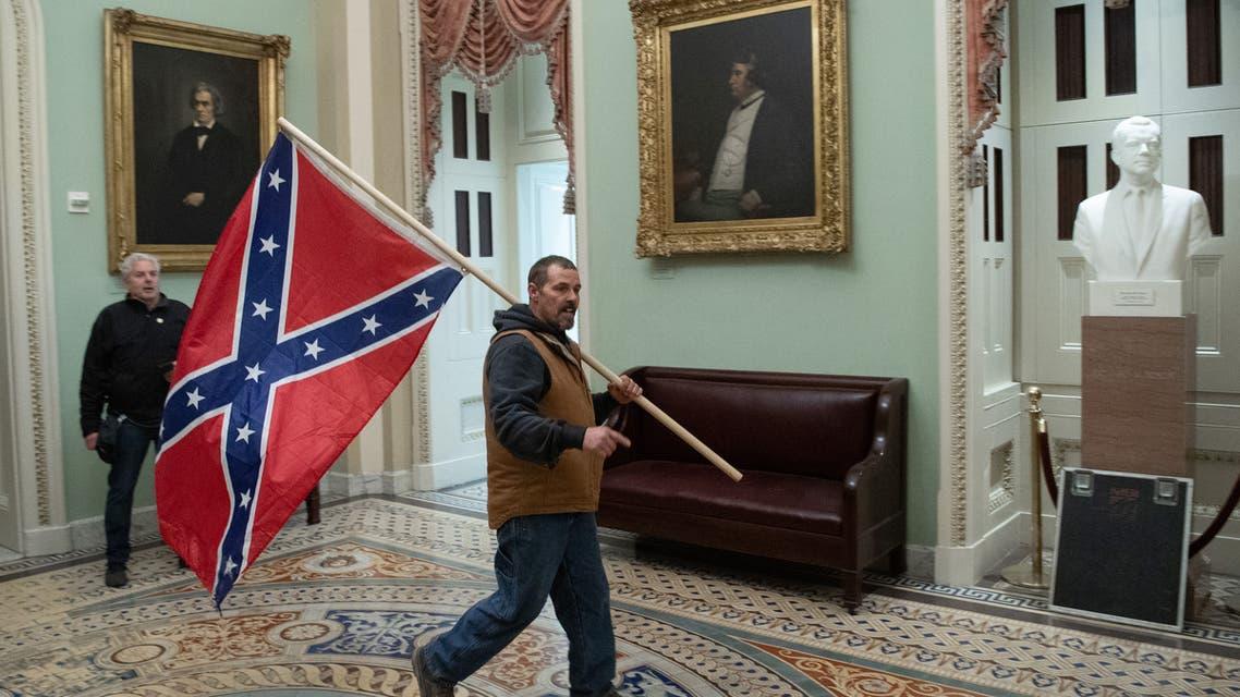 أحد المتظاهرين في مبنى الكونغرس حاملا العلم الفيدرالي (أرشيفية فرانس برس)