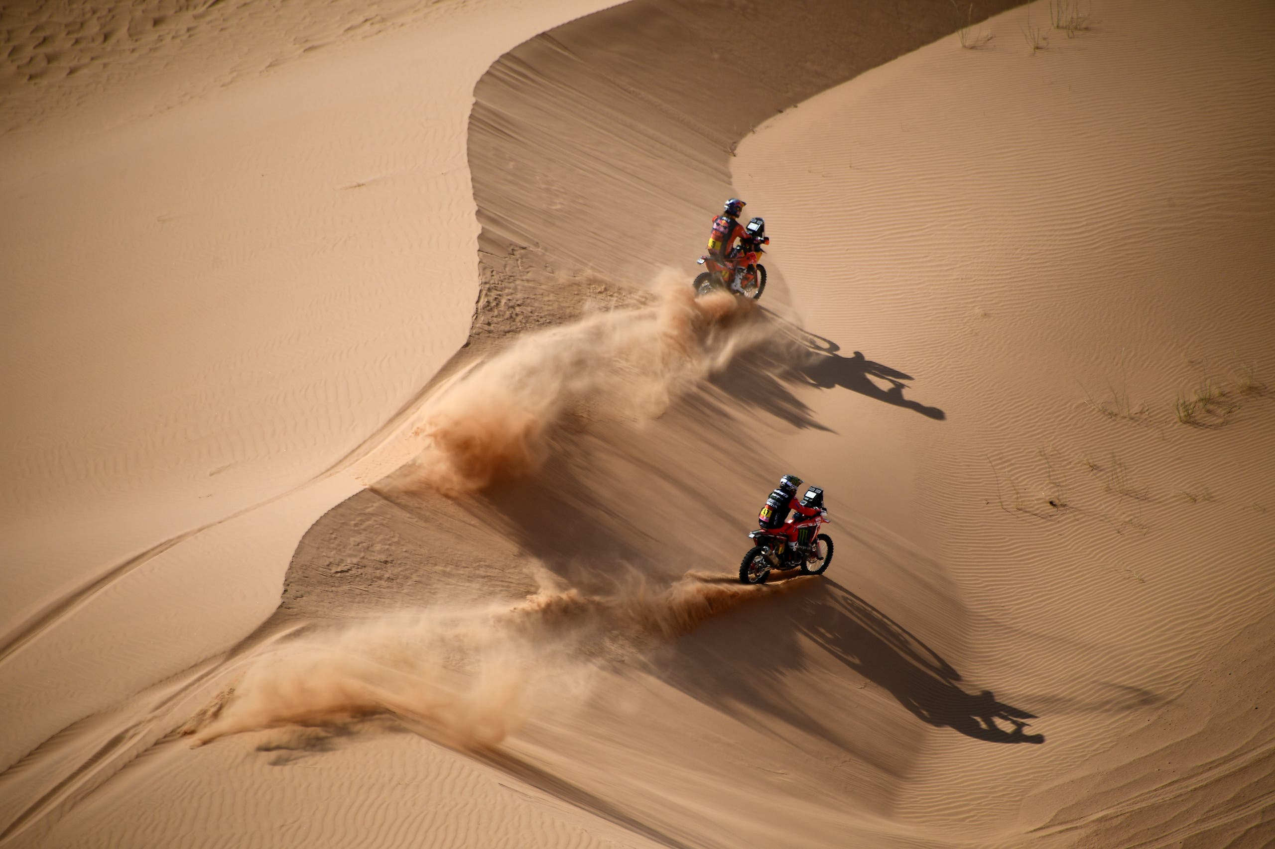 Australian biker Toby Price (top) and Argentinian biker Kevin Benavides compete during Stage 4 of the Dakar Rally 2021 between Wadi Ad-Dawasir and Saudi Arabia's capital Riyadh, on January 6, 2021. (AFP)