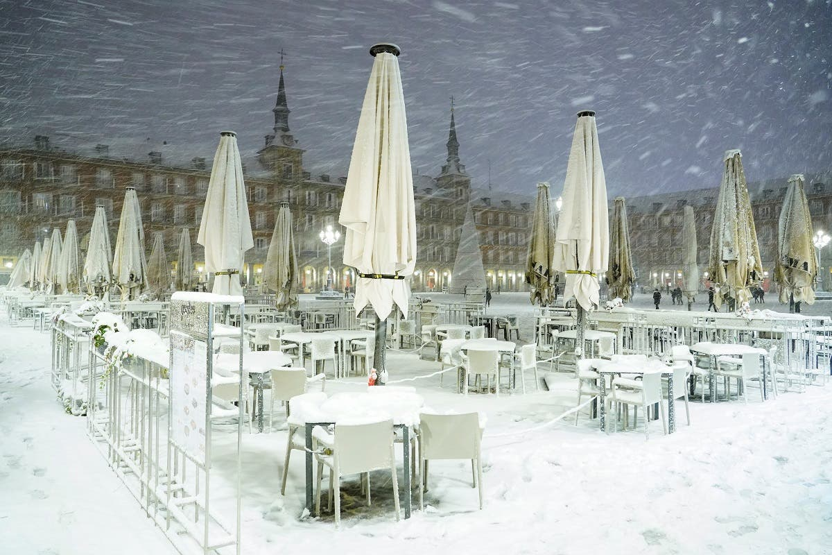 Snow-covered tables are seen at Plaza Mayor square during snowfall in Madrid, Spain. (Reuters)