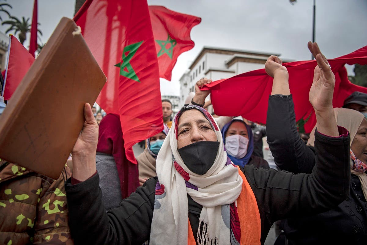 Moroccans celebrate in front of the parliament building in Rabat on December 13, 2020, after the US adopted a new official map of Morocco that includes the disputed territory of Western Sahara. (AFP)
