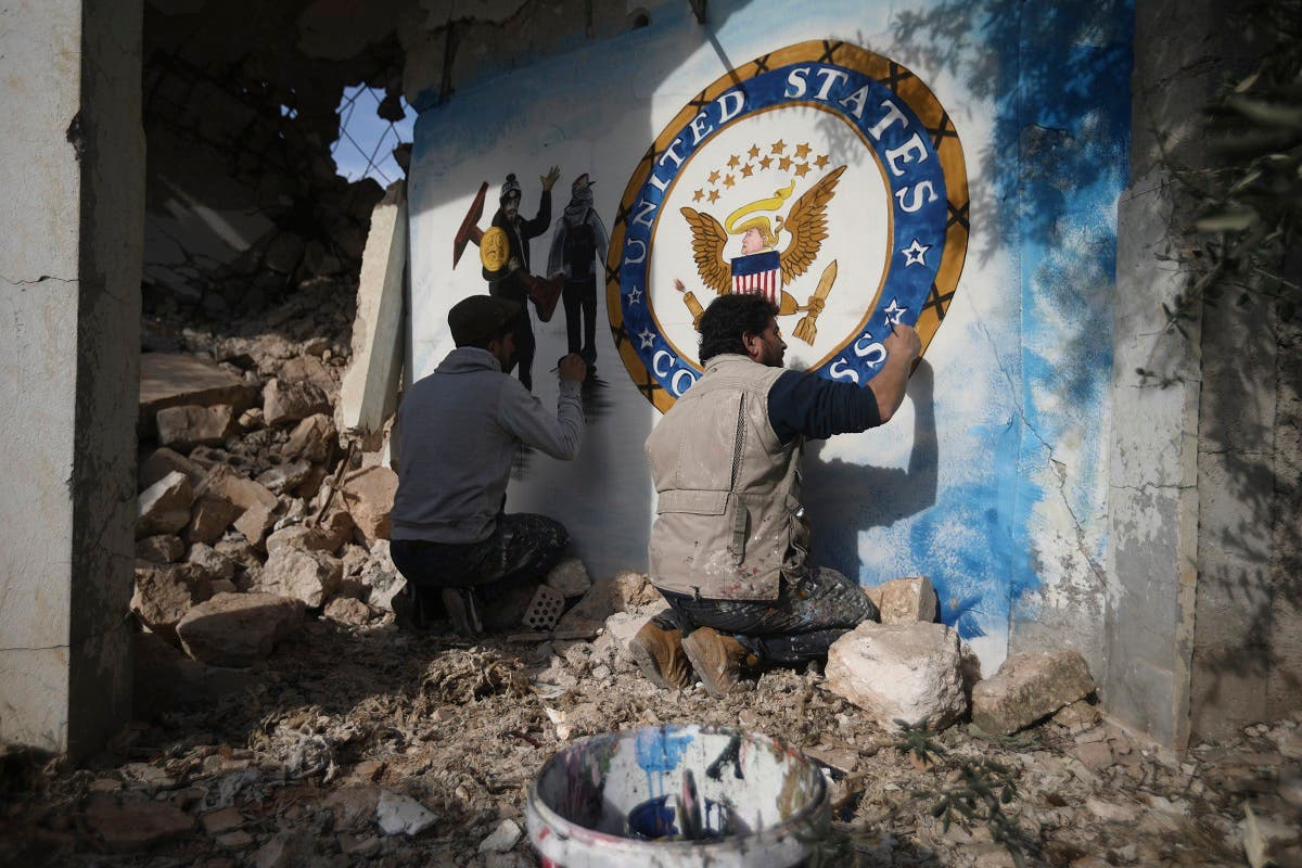 Syrian graffiti artist Aziz Al-Asmar, right, finishes work on his depiction of the events in Washington after the President Trump's supporters stormed the Capitol, on a wall of a house destroyed in an airstrike, in Binish, Idlib, Syria, Jan. 8, 2020. (AP/Ghaith Alsayed)