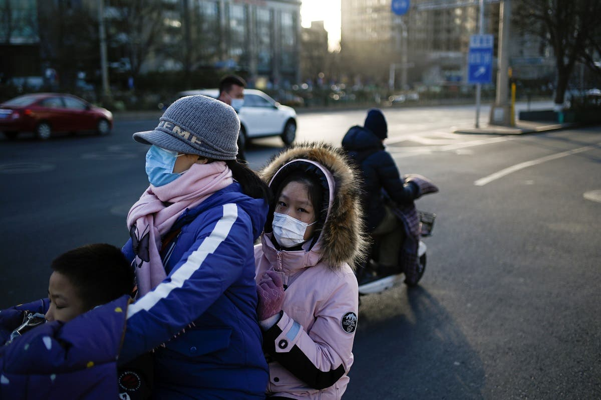 A woman and two children ride an electric bicycle along a road in Beijing on January 11, 2021. (Wang Zhao/AFP)