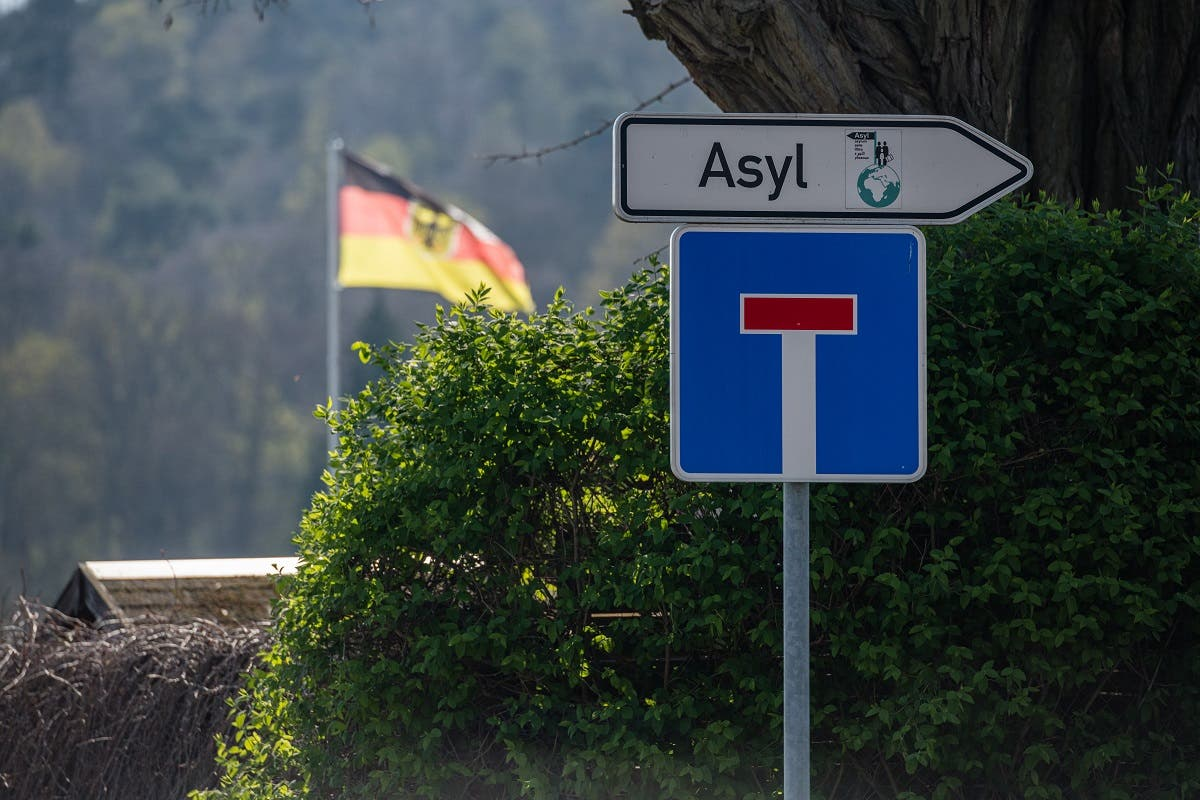 A traffic sign saying 'Asylum' and a one way street sign hang near the central contact point for asylum seekers (ZASt) in the state of Saxony-Anhalt on April 8, 2020, in Halberstadt, eastern Germany. (Jens Schlueter/AFP)