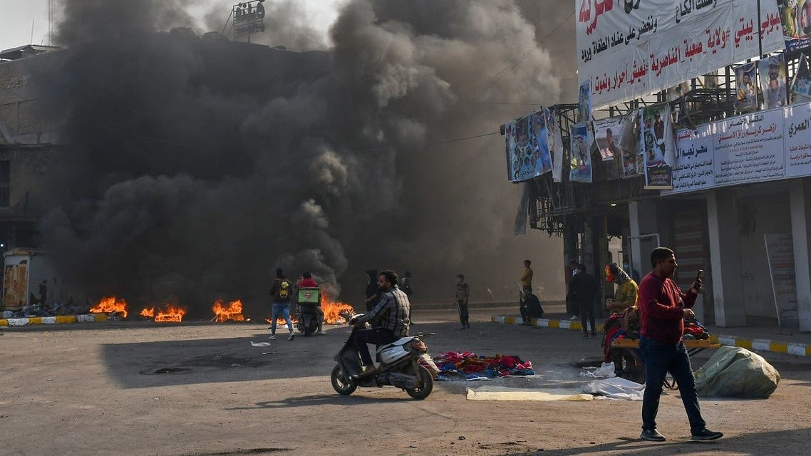 Iraqi protesters are pictured next to burning tires during clashes with police during anti-government demonstrations in the city of Nasiriyah in the Dhi Qar province in southern Iraq on January 10, 2021. (Asaad Niazi/AFP)