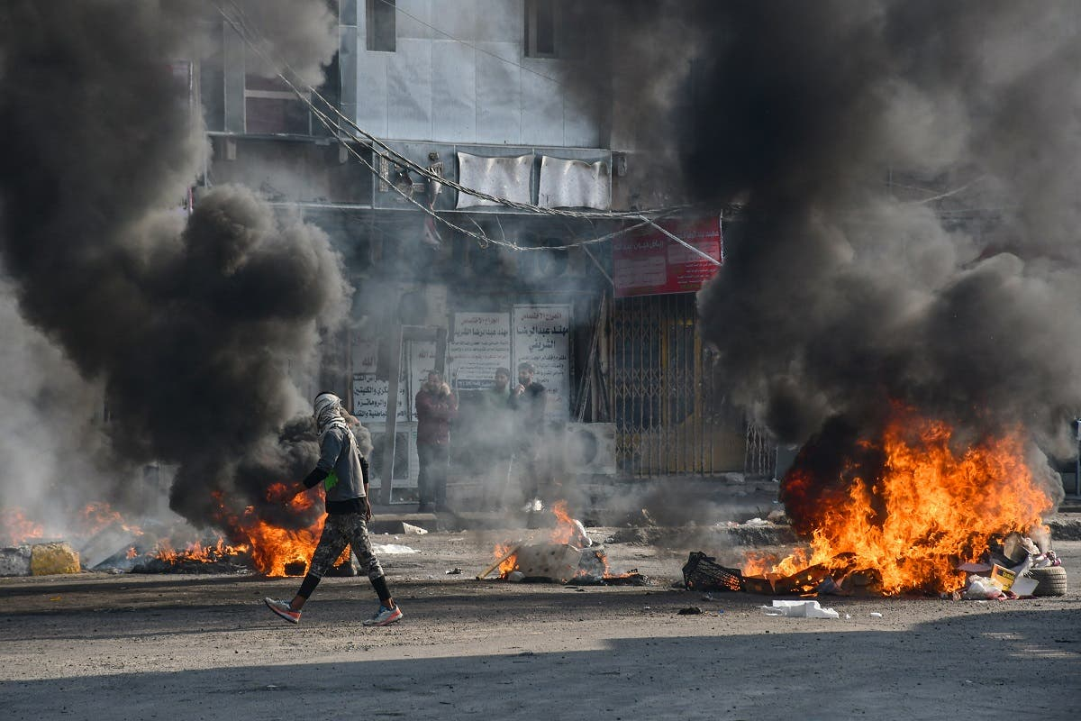 An Iraqi protester walks past burning tires during clashes with police during anti-government demonstrations in the city of Nasiriyah in the Dhi Qar province in southern Iraq on January 10, 2021. (Asaad Niazi/AFP)