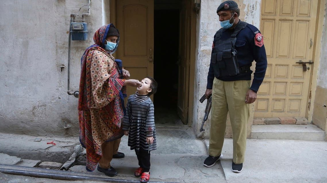 A police officer stand guard while a healthcare worker administers a polio vaccine to a child in Peshawar, Pakistan, on January 11, 2021. (AP)