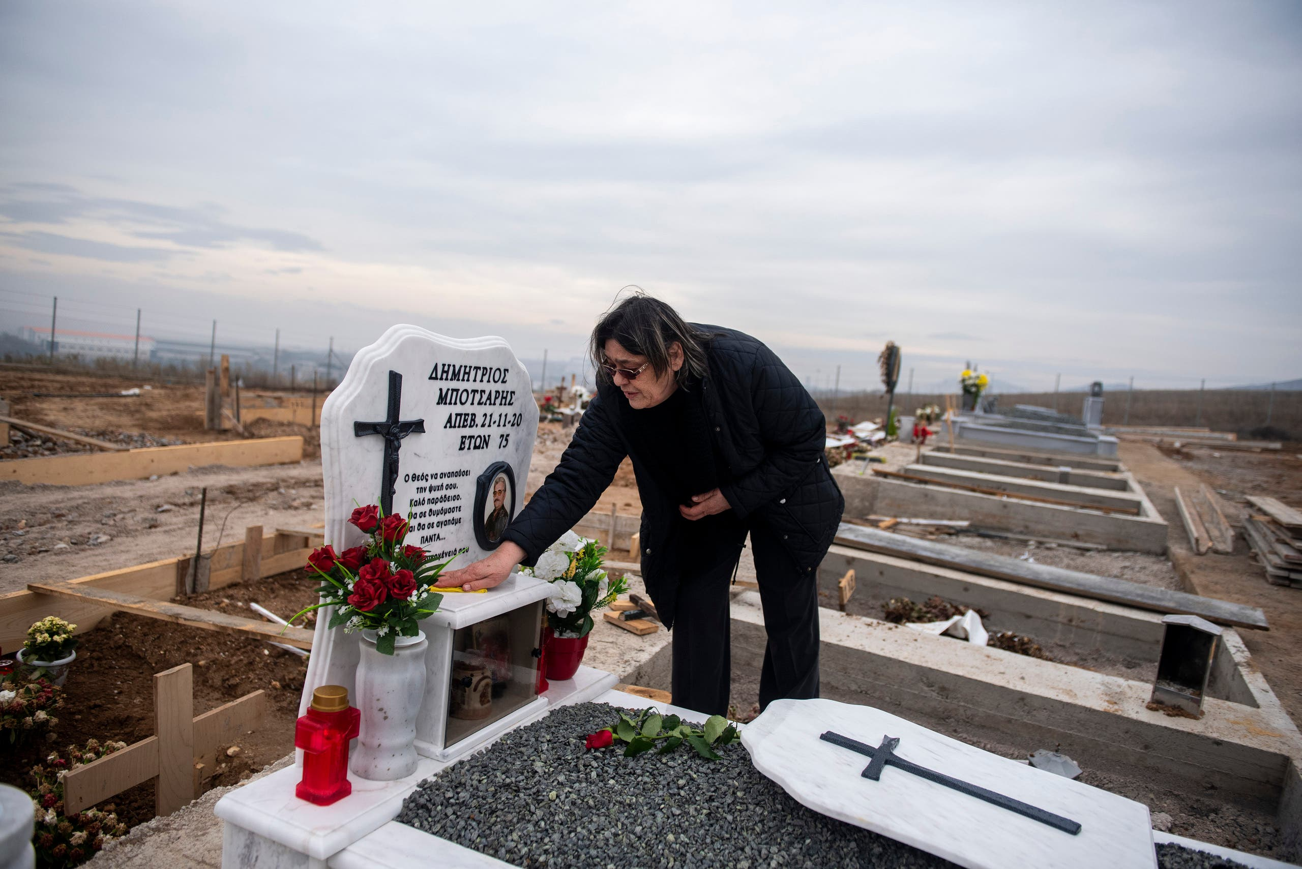 69 year-old Chrisanthi Botsari cleans the grave of her husband in a cemetery set up for victims of COVID-19, at the northern city of Thessaloniki, Greece. (AP)