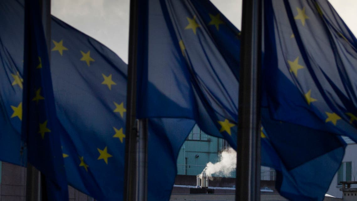 Smoke rises from a chimney behind EU flags fluttering in the wind outside EU headquarters in Brussels, Belgium. (AP)
