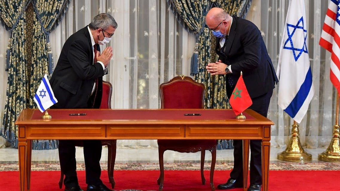 Israeli Director General of the Ministry of Water Resources Yechezkel Lifshitz (L) and Moroccan Director General of Water Hammou Bensaadout greet each other before signing an agreement at the Royal Palace in Rabat, December 22, 2020. (Fadel Senna/AFP)