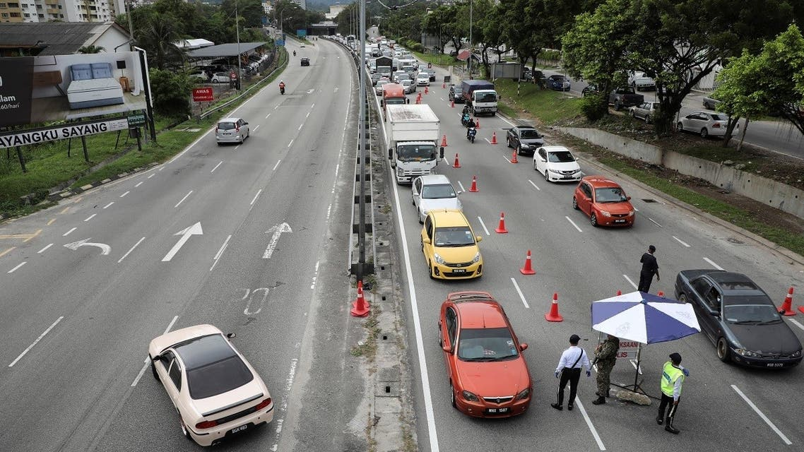 Cars drive past a roadblock as a lockdown is enforced due to the coronavirus disease (COVID-19) outbreak, in Kuala Lumpur, Malaysia, on  January 13, 2021. (Reuters)