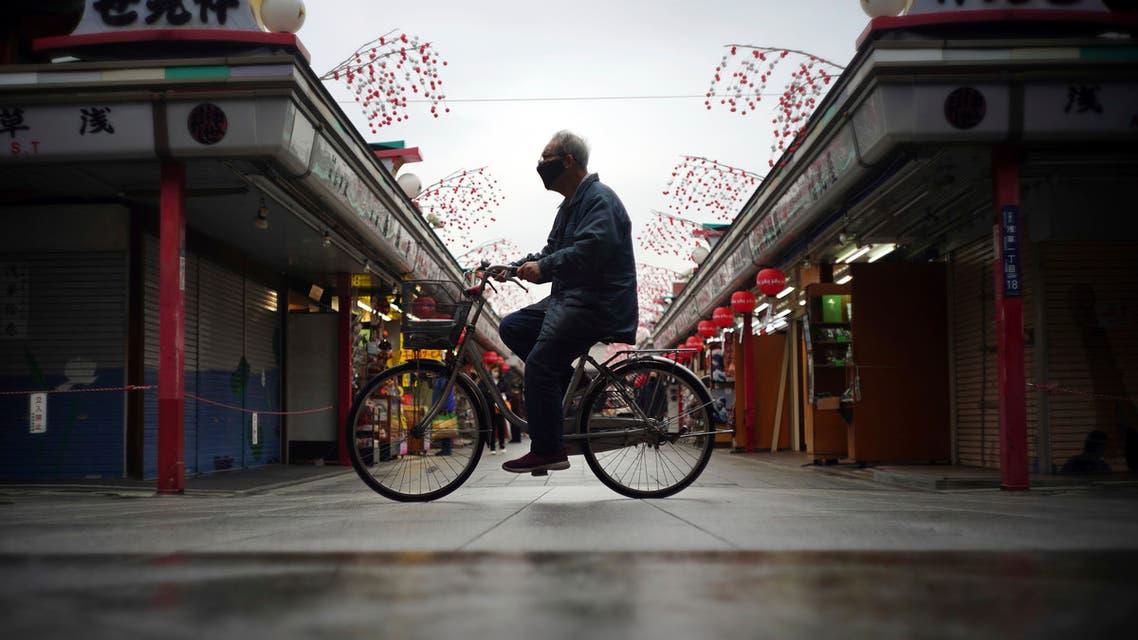 A man rides a bicycle through a shopping arcade in Tokyo. (AP)