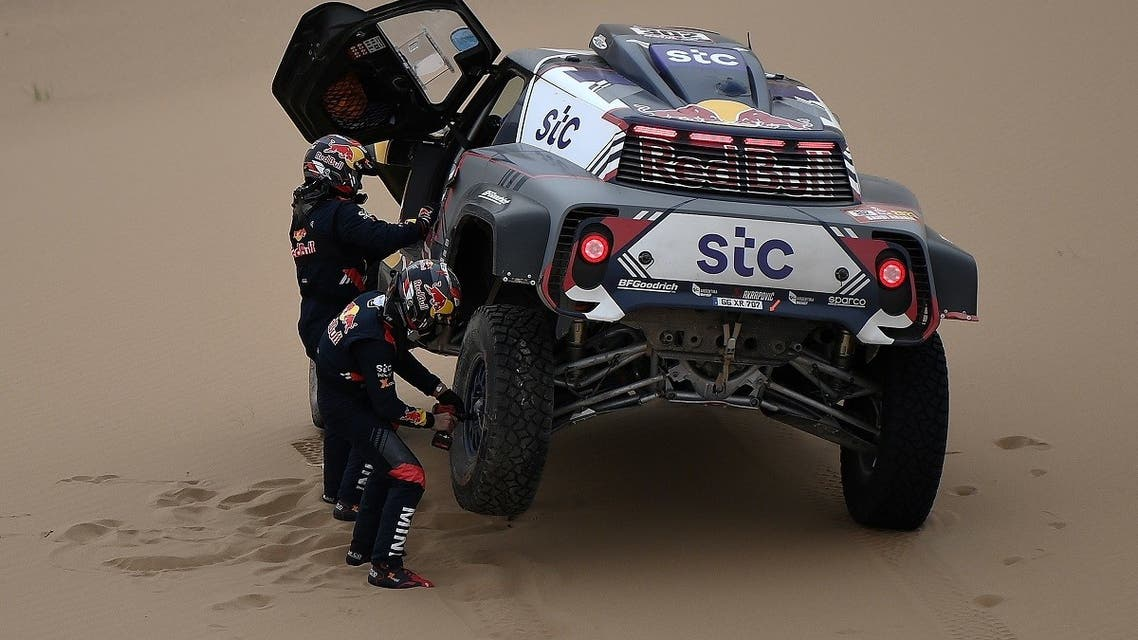 Mini's driver Stephane Peterhansel and his co-driver Edouard Boulanger of France change a tire as they compete during the Stage 11 of the Dakar 2020 between Alula and Yanbu, Saudi Arabia. (AFP)