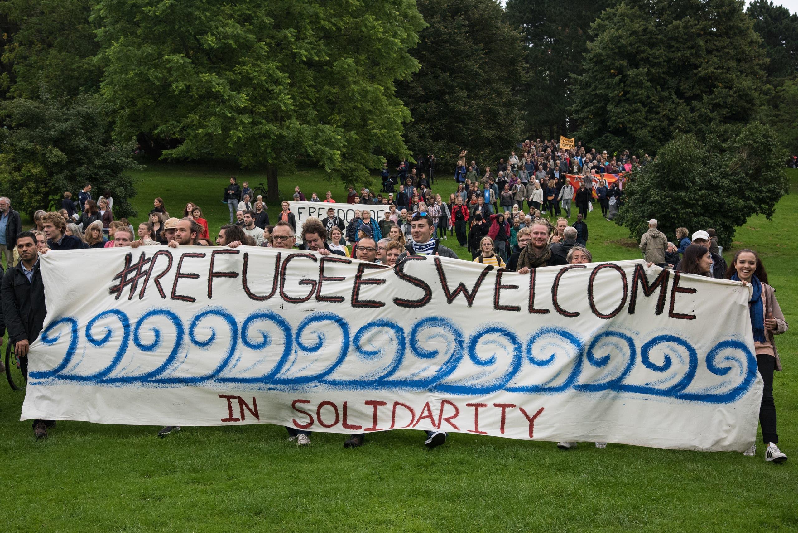 سكان في الدنمارك يرفعون لافتة ترحب باللاجئين في كوبنهاغن في 2015