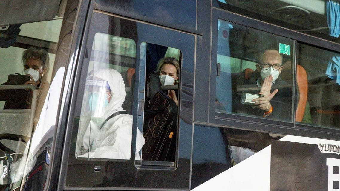 Members of the World Health Organisation (WHO) team tasked with investigating the origins of the coronavirus disease (COVID-19) pandemic sit on a bus while leaving Wuhan Tianhe International Airport in Wuhan, Hubei province, China, on January 14, 2021. (Reuters)_1068089859_RC2H7L9WN4UA_RTRMADP_3_HEALTH-CORONAVIRUS-WHO-CHINA