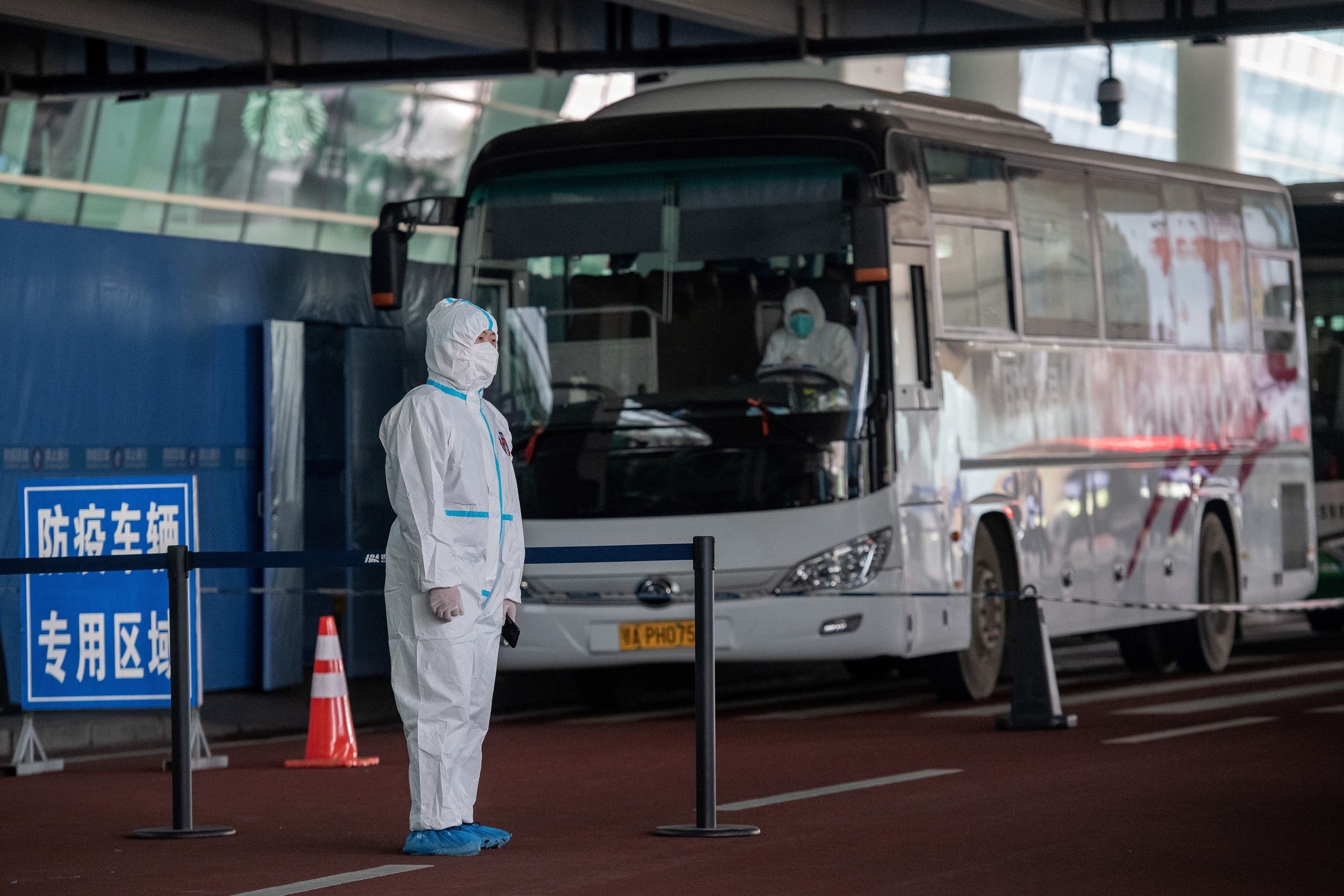 Health workers stand next to buses at a cordoned-off section at the international arrivals area. (AFP)