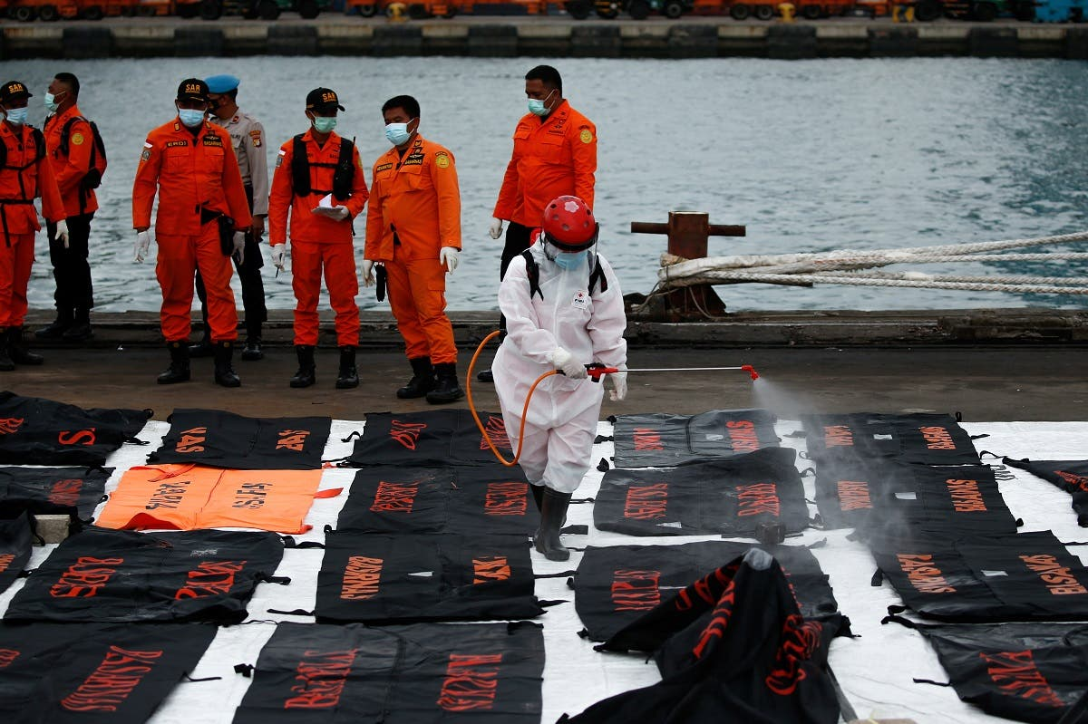An Indonesian Red Cross worker sprays disinfectant on bags containing body parts of passengers of the Sriwijaya Air flight SJ 182, which crashed into the Java sea, at Tanjung Priok port in Jakarta, Indonesia, on January 14, 2021. (Reuters)