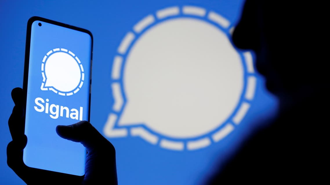 A woman holds a smartphone displaying the Signal messaging app logo, which is also seen near her, in this illustration taken January 13, 2021. REUTERS/Dado Ruvic