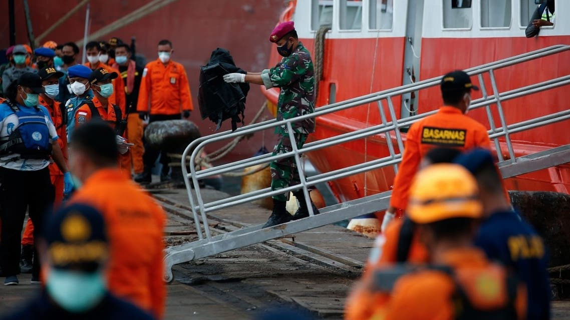 An Indonesian Navy member carries a bag containing body parts of passengers of the Sriwijaya Air flight SJ 182, which crashed into the Java sea, at Tanjung Priok port in Jakarta, Indonesia, on January 14, 2021. (Reuters)