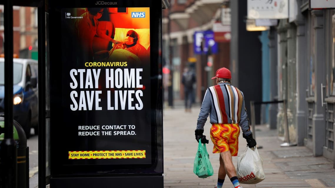 A shopper walks past NHS signage promoting Stay Home, Save Lives on a bus shelter in Chinatown, central London. (AFP)