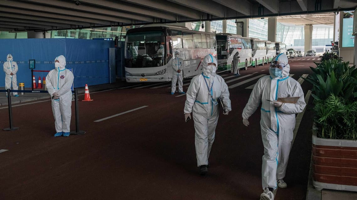 Health workers wearing a personal protection suit stands next to buses at a cordoned-off section at the international arrivals area. (AFP)