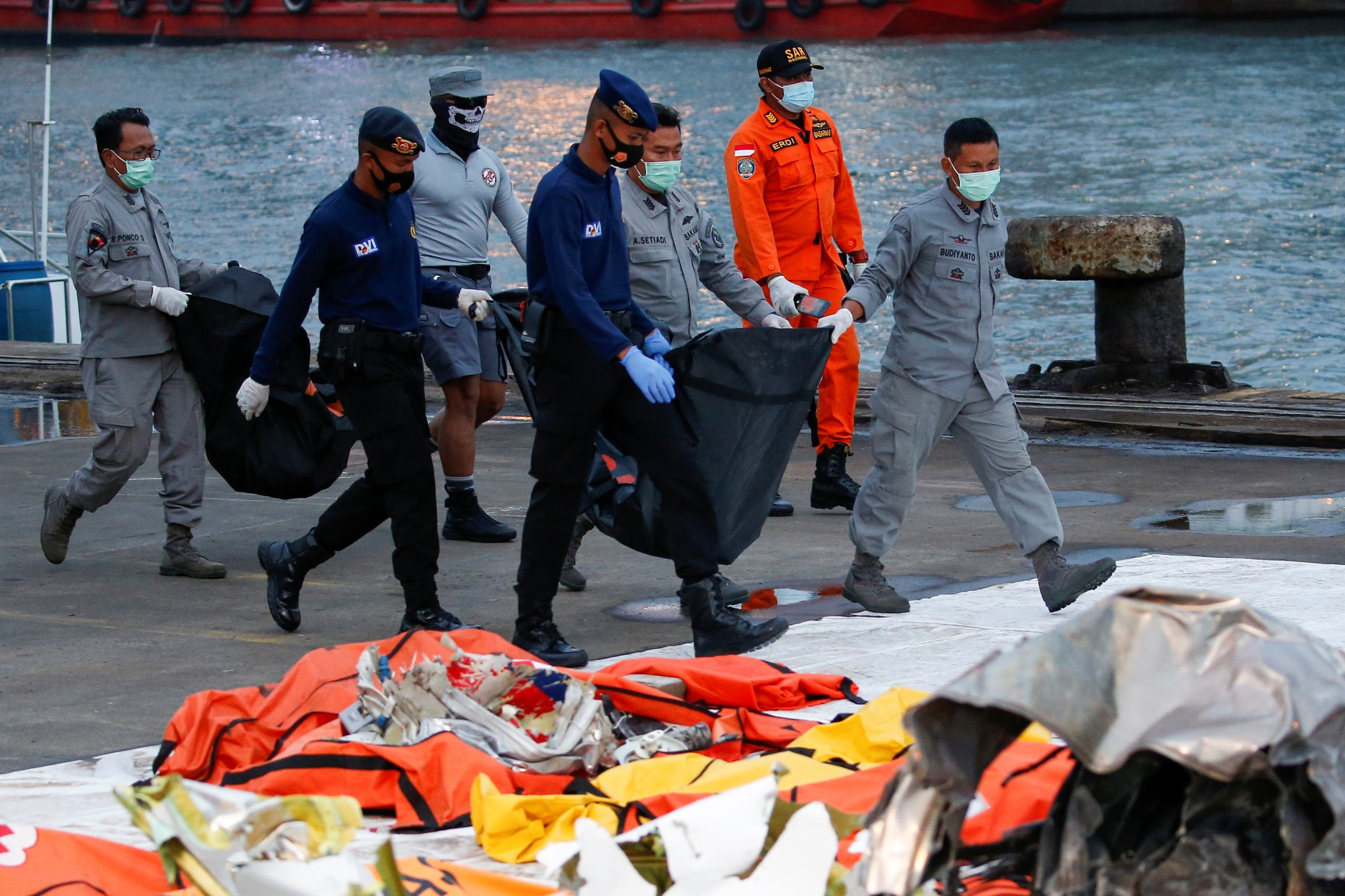 Indonesian DVI and navy personnel carry bags with body parts of the passengers of Sriwijaya Air flight SJ-182, which crashed to the sea, at Tanjung Priok port in Jakarta, Indonesia. (Reuters)