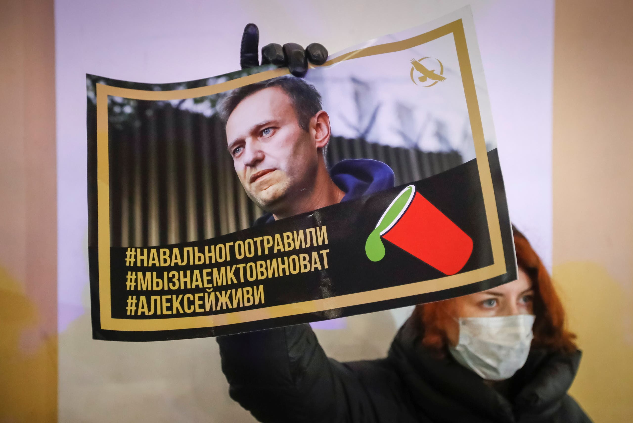 An activist holds a portrait of opposition politician Alexei Navalny during a picket in his support in St Petersburg, Russia December 22, 2020. (Reuters)