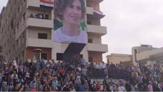 عکس اسما اسد در حالی که از سه طبقه یک زمین ورزشی در منطقه بابا امر در حمص آویزان شده است