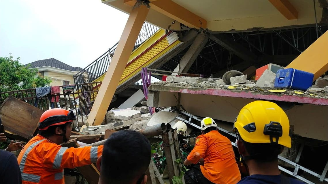 Members of a search and rescue agency team dig through rubble after an earthquake, in Mamuju, West Sulawesi Province, Indonesia January 15, 2021. (Basarnas Sulbar via Reuters)