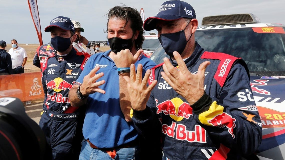 Stephane Peterhansel and Co-Driver Edouard Boulanger celebrate after winning the Dakar Rally in the car category with Dakar Rally director David Castera. (Reuters)