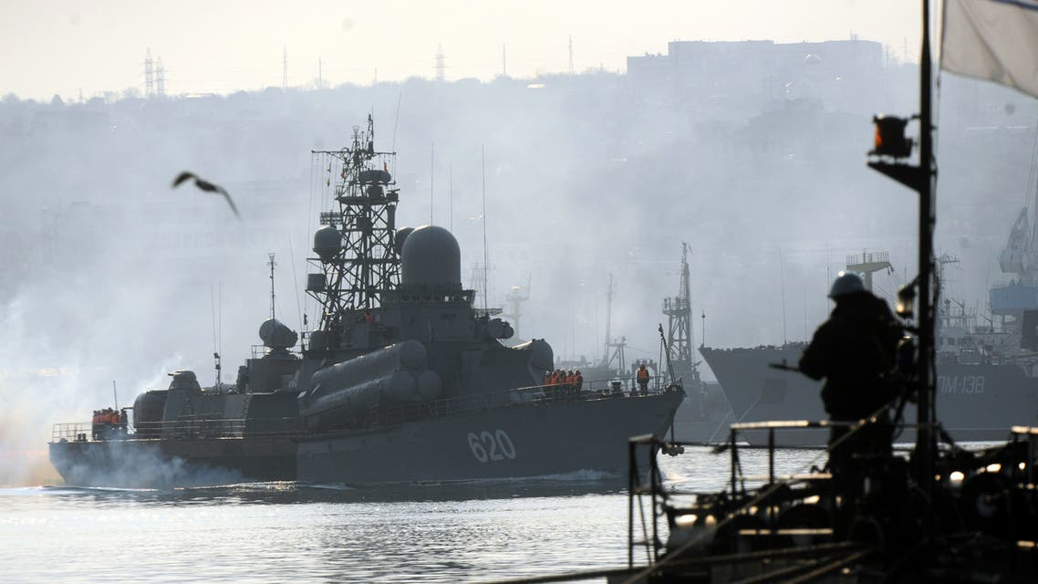 A Ukrainian sailor guards on the ship Ternopil as Russian guided missile destroyer Bespokoynyy sails near by in Sevastopol bay on March 12, 2014. Ukraine will not intervene militarily in the separatist peninsula of Crimea, in order to avoid exposing its eastern border, Ukraine's acting president told AFP Tuesday in an exclusive interview. AFP PHOTO/ VIKTOR DRACHEV